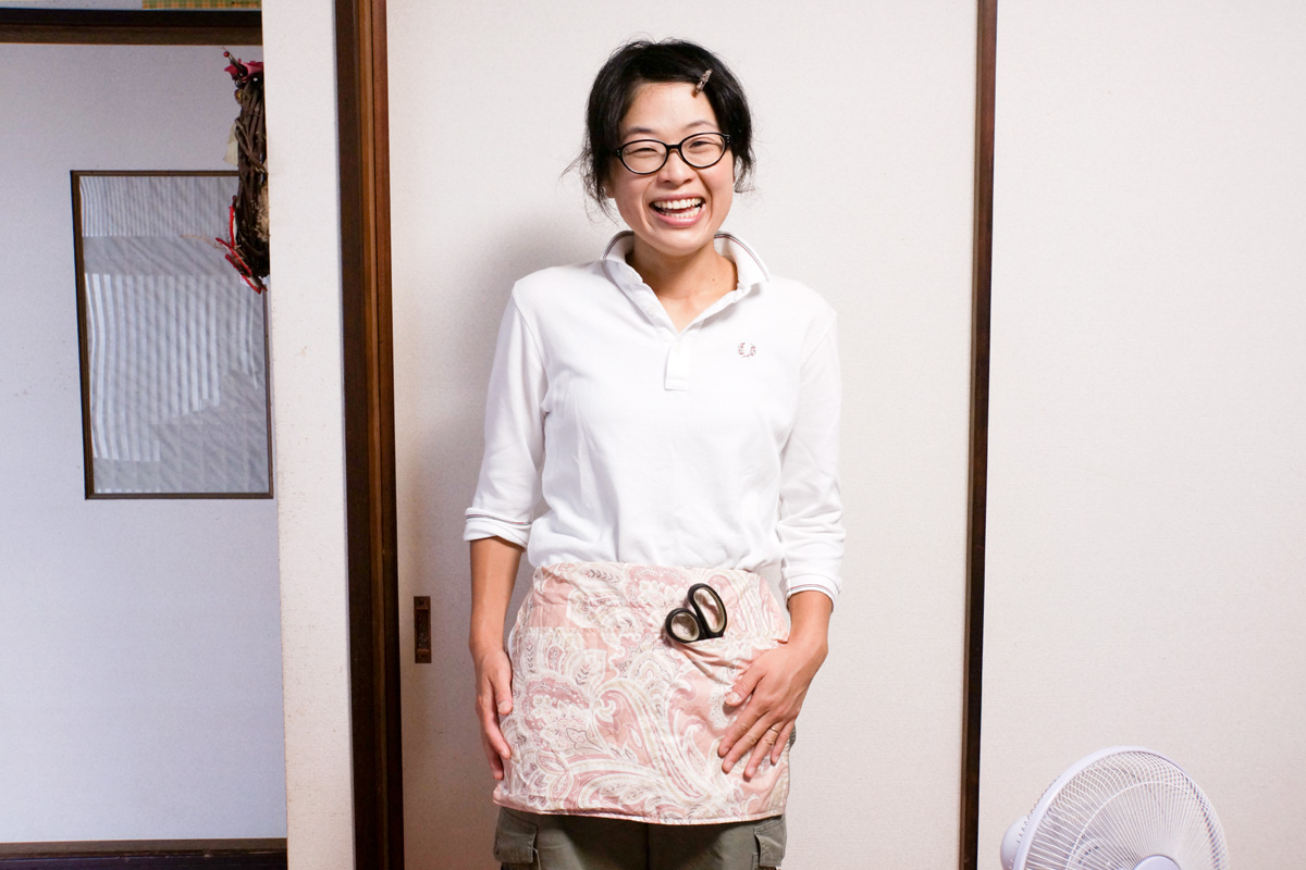 郁子さんの手作り作業エプロン。何でも入るポケットが便利。妊婦もお腹の大きさに合わせて紐の長さを調節できる。